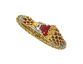 An 18ct gold, diamond and enamel bracelet, by Kutchinsky Modelled as a red enamelled lion's head, the mane with black enamel accents, with green gem eyes, black enamel and brilliant-cut diamond snout, clutching a brilliant-cut diamond loop in its jaw, to a matching red enamel flexible bangle with brilliant-cut diamond collar, internal diameter 5.4cm, London hallmark  Maker's mark Kld. Estimate £ 3,500-4,000.