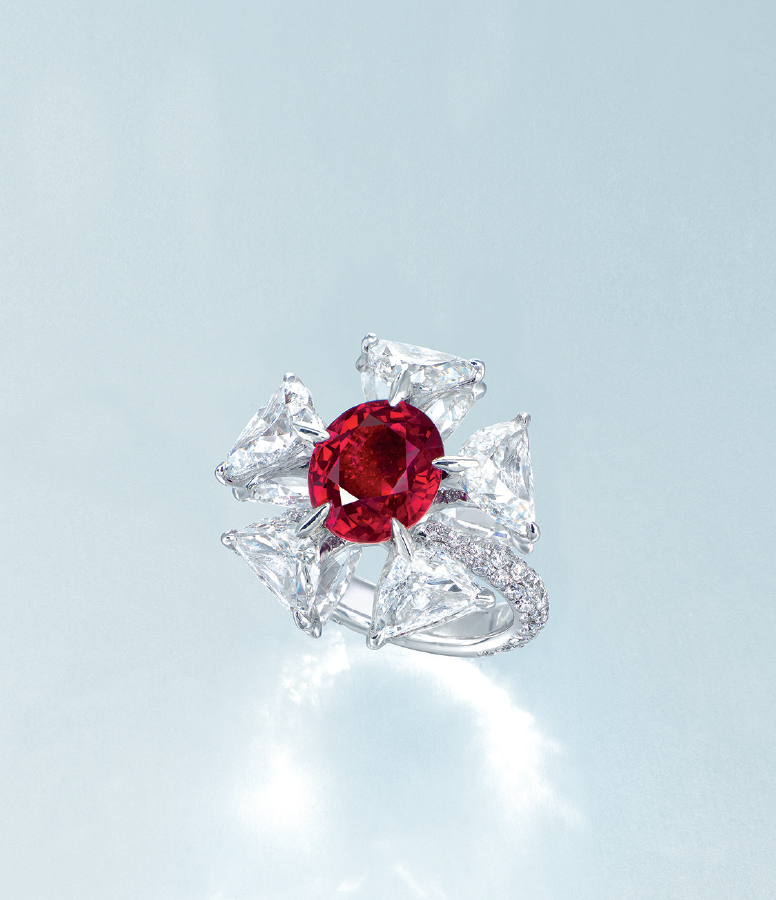 A superb important ruby and diamond ring by Etcetera. Centering on an oval-shaped ruby weighing approximately 5.11 carats, within a half-moon diamond surround, each set to the reverse with a triangular-shaped diamond, elevated over a brilliant-cut diamond gallery, extending to the three quarter-hoop, mounted in 18k white gold.