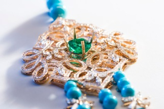 Adjusting the central emerald on the gem-set motif.