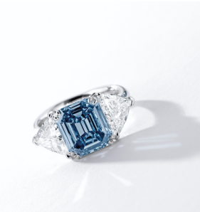 Centring on an emerald-cut fancy vivid blue diamond weighing 3.32 carats, flanked by two trilliant-cut diamonds together weighing approximately 2.00 carats, mounted in 18 karat white gold.