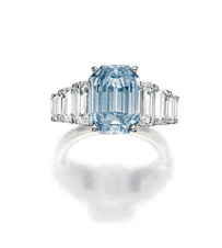 Set with an emerald-cut fancy intense blue diamond weighing 3.72 carats, flanked with inverted emerald-cut diamonds, accented by pavé-set brilliant-cut diamonds, the diamonds together weighing approximately 2.20 carats, mounted in 18 karat white gold.