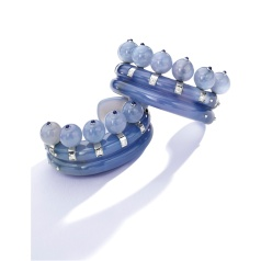 The double-fluted cuff-bracelets composed of carved chalcedony in the form of stylized crowns, bordered by 14 chalcedony beads, each bead topped by a cabochon sapphire, further decorated by old European-cut diamonds weighing approximately 2.80 carats, internal circumference 6 and 5¾ inches; 1932-1937. With fitted box. Estimate: $400-600,000.